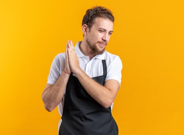 Blij uitziende jonge mannelijke kapper die een uniform draagt, hand in hand samen geïsoleerd op een gele muur