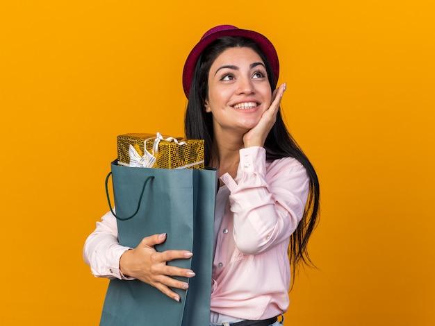 Blij uitziende jonge, mooie meid met een feesthoed die een cadeauzakje vasthoudt en de hand op de wang legt