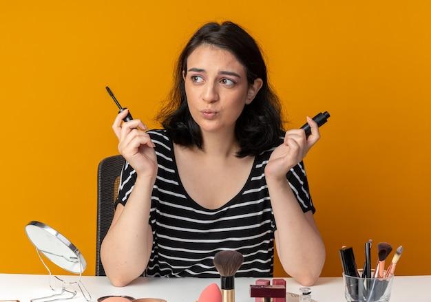 Blij uitziende jonge, mooie meid zit aan tafel met make-uptools met mascara geïsoleerd op een oranje muur