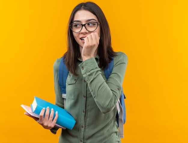 Blij uitziende jonge schoolvrouw die een rugzak draagt met een bril die boeken vasthoudt en nagels bijt