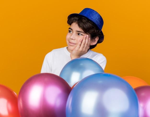 Blij uitziende kleine jongen met een blauwe feesthoed die achter ballonnen staat en hand op de wang legt die op een oranje muur is geïsoleerd