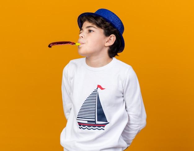 Blij uitziende kleine jongen met een blauwe feestmuts die een feestfluitje blaast dat op een oranje muur wordt geïsoleerd