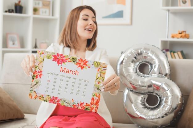 Blij uitziende zijvrouw op gelukkige vrouwendag met kalender zittend op de bank in de woonkamer