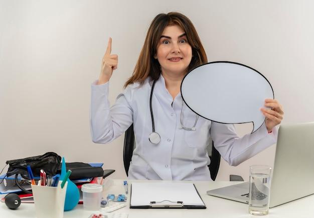 Blij van middelbare leeftijd vrouwelijke arts die het dragen van medische mantel met stethoscoop zittend aan bureau werkt op laptop met medische hulpmiddelen houdt praatjebel en wijst naar omhoog op geïsoleerde witte muur