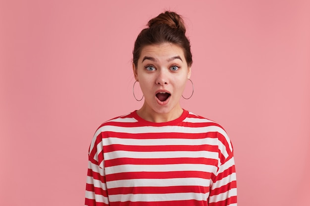 Blij verbaasd sproeten jongedame, hoorde heel goed nieuws! kijkend naar de camera met wijd open mond geïsoleerd op roze achtergrond.