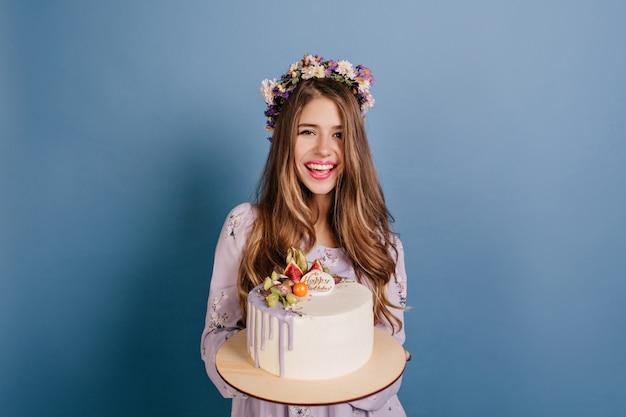 Blij verjaardagsvrouw die grote smakelijke cake houdt en glimlacht