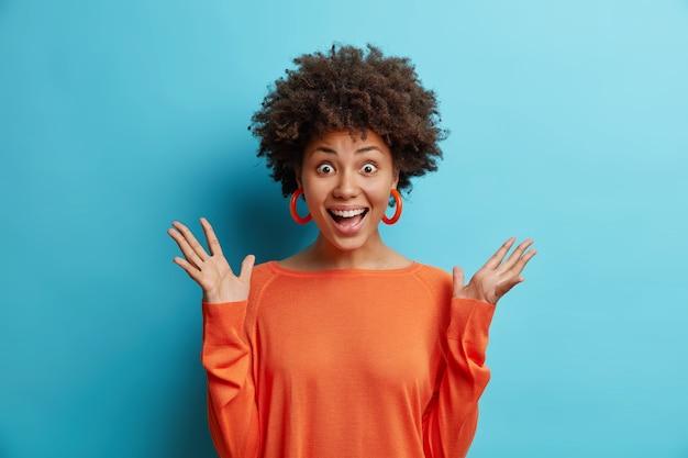 Blij verrast aantrekkelijke afro-amerikaanse vrouw hand opsteken reageert op geweldige onverwachte relevantie