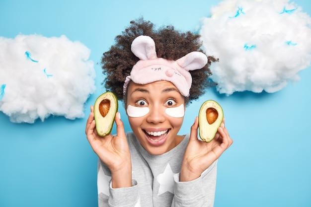 Blij verrast afro-amerikaanse vrouw houdt twee helften van verse rijpe avocado ondergaat gezichtsverzorgingsprocedures past patches toe onder ogen gekleed in nachtkleding slaapmasker op voorhoofd geïsoleerd op blauwe muur