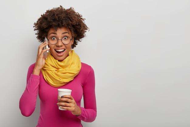 Blij verrast afro-amerikaanse vrouw krijgt geweldig nieuws tijdens gesprek via smartphone, heeft koffiepauze