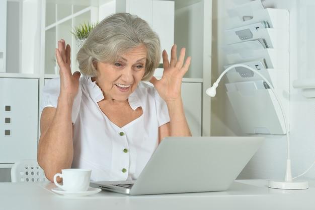 Blij verrast bejaarde vrouw die op laptop op kantoor werkt