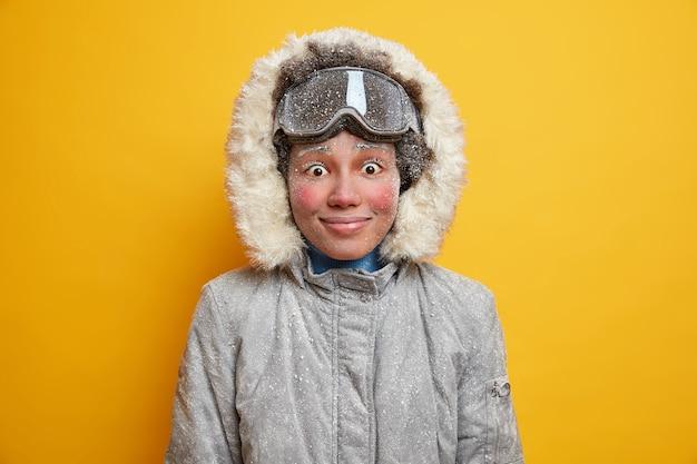 Blij verrast bevroren vrouw geniet van favoriete hobby tijdens wintervakantie heeft vrolijke uitdrukking rode wangen als lange tijd doorbrengt tijdens koude dagen.