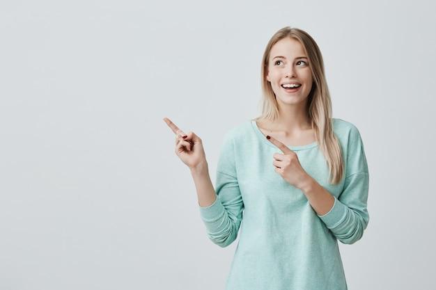 Blij verrast blonde jonge vrouw breed glimlachend, wijzende vingers weg, iets interessants en opwindend laten zien