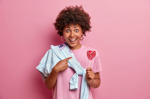 Blij verrast donkere vrouw wijst naar zichzelf, stelt vraag, houdt heerlijke lolly vast, draagt trui vastgebonden over schouder geïsoleerd op roze muur. tiener poseert met zoete snoep