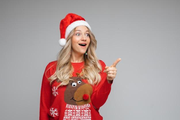 Blij verrast jong meisje in kerstmuts en rode kerstmis nieuwjaarssweater met de vinger opzij, studioportret op grijs