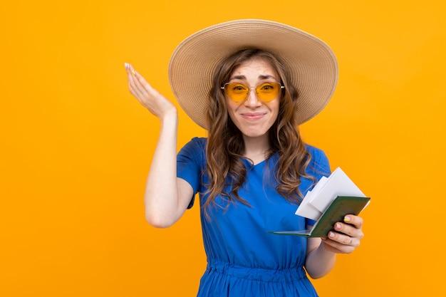 Blij verrast jonge vrouw in een blauwe jurk en een strooien hoed en zonnebril met een paspoort en vakantie tickets op geel