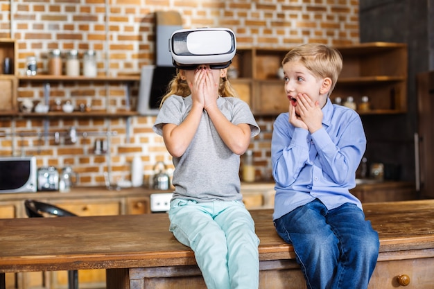 Blij verrast kleine broers en zussen die vr-apparaat testen terwijl ze in de keuken zitten