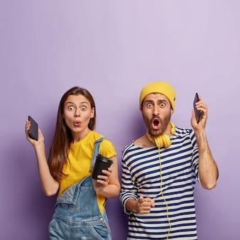 Blij verrast leuk stel heeft samen plezier, steekt de hand op met smartphones, hoort aangename muziek, drinkt koffie, geniet van vrije tijd,