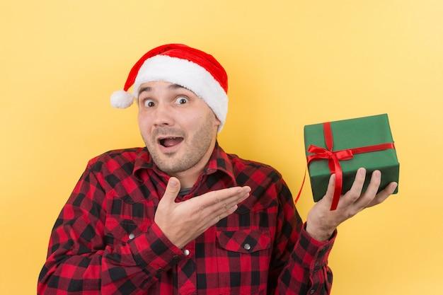 Blij verrast man in een rode hoed met een geschenk met bewondering op zijn gezicht