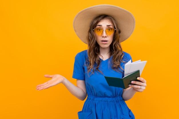 Blij verrast meisje in een blauwe jurk en een strooien hoed en zonnebril met een paspoort en vakantie kaartjes op geel