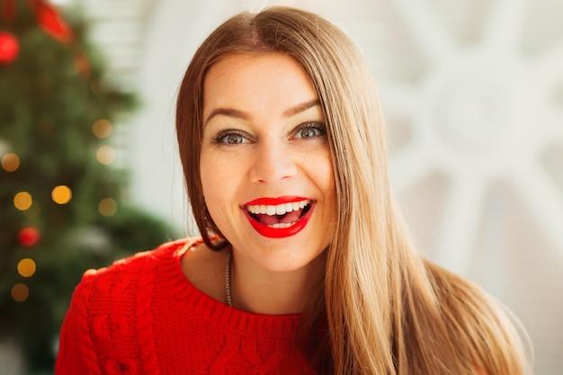 Blij verrast meisje op een kerstavond. vrolijke emotionele vrouw met rode lippen die met haar witte tanden glimlachen