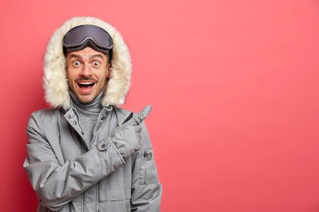 Blij verrast opgewonden man snowboard rider in winterjas ontspant nadat het skiën actieve dag van recreatie punten weg op lege ruimte heeft.