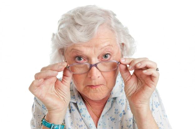 Blij verrast oude senior dame kijkt door haar bril op wit wordt geïsoleerd