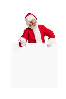 Blij verrast santa claus wijzend op lege advertentie banner achtergrond met kopie ruimte. glimlachende hogere mens die bij witte spatie van lege affiche toont