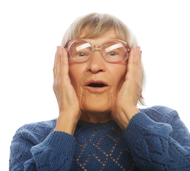 Blij verrast senior vrouw kijkt naar camera geïsoleerd op een witte achtergrond