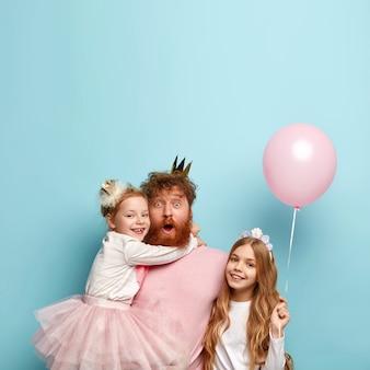 Blij verrast vader vergeet wat attributen te kopen voor vakantie, brengt vrije tijd door met twee schattige dochters, viert een speciale gelegenheid, houdt een ballonfeest, geïsoleerd over blauwe muur. vaderdag