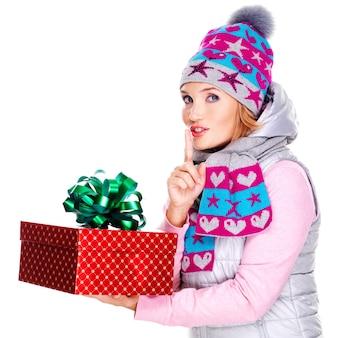 Blij verrast vrouw met een kerstcadeau in een winter bovenkleding op wit wordt geïsoleerd
