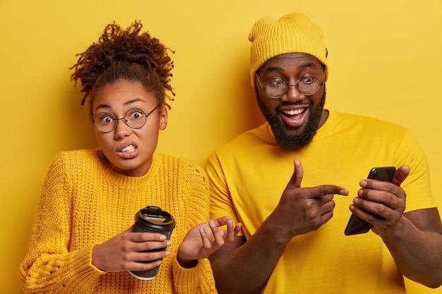 Blij verrast zwarte man wijst in scherm van smartphoneapparaat