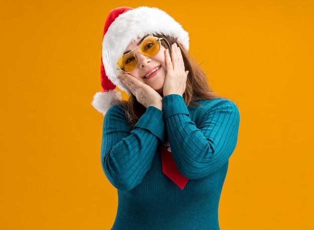 Blij volwassen blanke vrouw in zonnebril met kerstmuts en santa stropdas zet handen op gezicht geïsoleerd op oranje muur met kopie ruimte