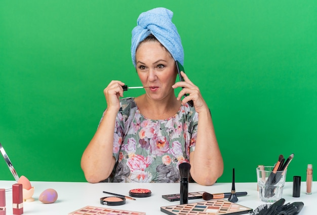Blij volwassen blanke vrouw met gewikkeld haar in een handdoek zittend aan tafel met make-up tools praten over de telefoon lipgloss toe te passen