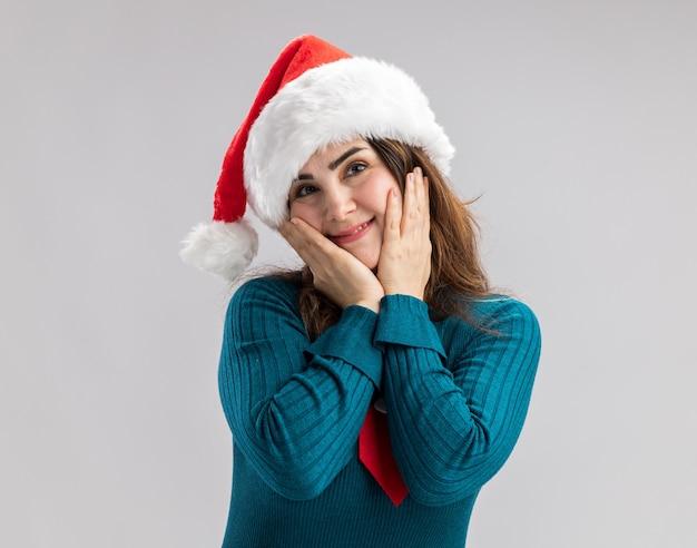 Blij volwassen blanke vrouw met kerstmuts en kerststropdas legt handen op gezicht geïsoleerd op een witte muur met kopieerruimte