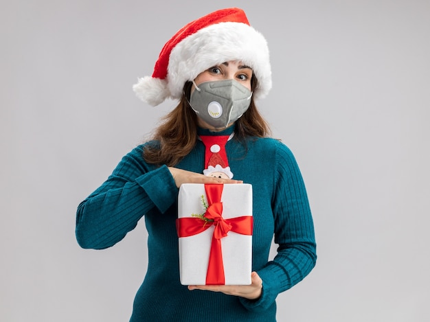 Blij volwassen blanke vrouw met kerstmuts en santa stropdas dragen van medisch masker met kerst geschenkdoos geïsoleerd op een witte muur met kopie ruimte