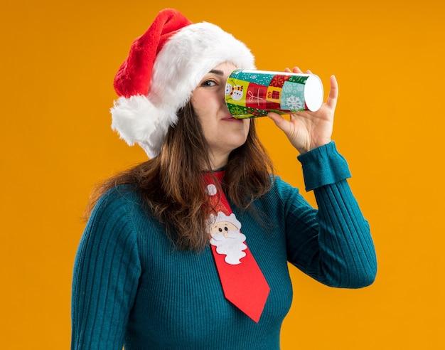 Blij volwassen blanke vrouw met kerstmuts en santa stropdas drankjes uit papieren beker geïsoleerd op een oranje achtergrond met kopie ruimte