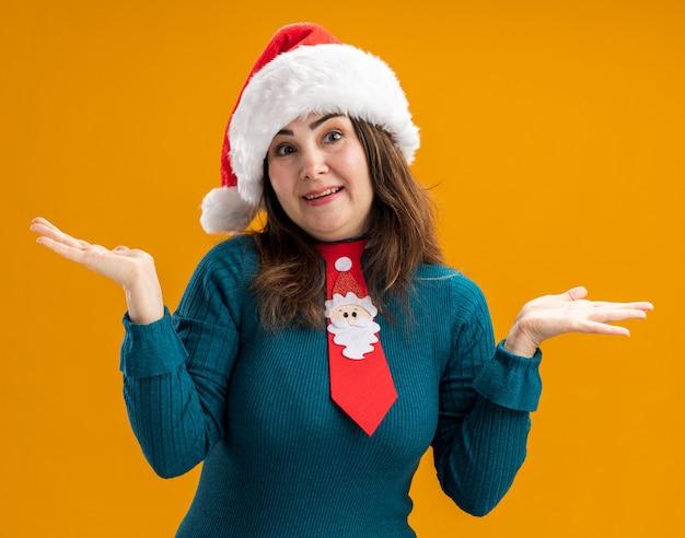 Blij volwassen blanke vrouw met kerstmuts en santa stropdas hand in hand open geïsoleerd op een oranje achtergrond met kopie ruimte