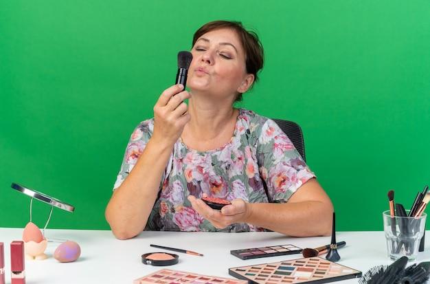Blij volwassen blanke vrouw zittend aan tafel met make-up tools houden blozen en blazen op make-up borstel geïsoleerd op groene muur met kopie ruimte