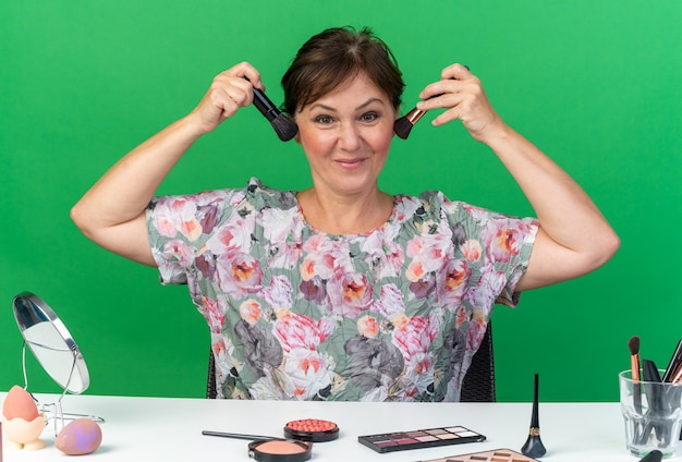 Blij volwassen blanke vrouw zittend aan tafel met make-up tools met make-up kwasten