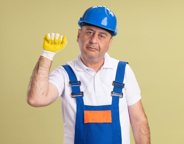 Blij volwassen bouwer man in uniform dragen van beschermende handschoenen houdt vuist omhoog geïsoleerd op olijfgroene muur
