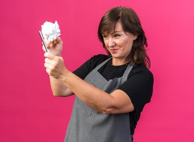 Blij volwassen kaukasische vrouwelijke kapper in uniform houden en kijken naar scheermes en scheerkwast met schuim bovenop geïsoleerd op roze achtergrond met kopie ruimte