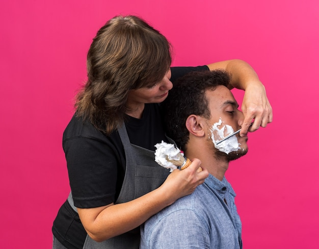 Blij volwassen kaukasische vrouwelijke kapper in uniform houden scheerkwast met schuim en scheren baard van jonge man met scheermes kijken naar hem geïsoleerd op roze achtergrond met kopie ruimte