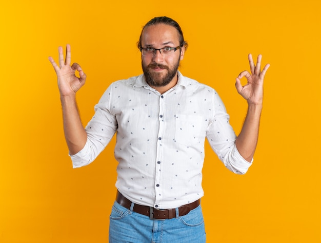 Blij volwassen knappe man met bril kijken naar camera doen ok teken geïsoleerd op oranje muur