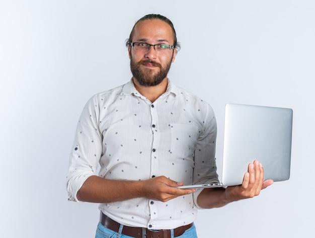 Blij volwassen knappe man met bril met laptop kijken naar camera geïsoleerd op een witte muur