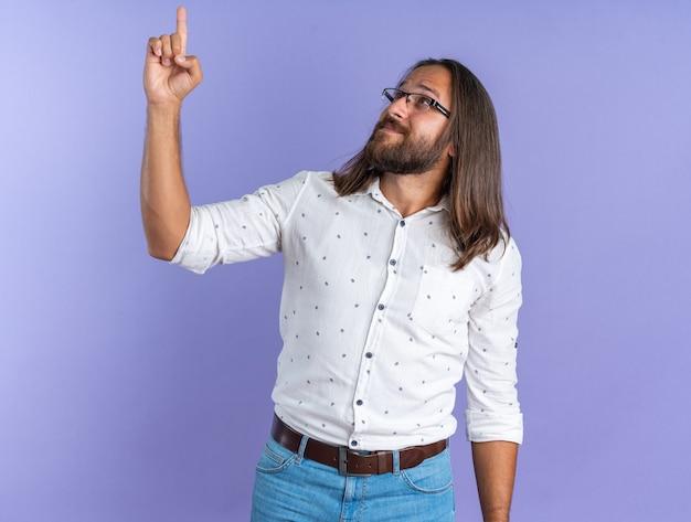 Blij volwassen knappe man met bril op zoek en omhoog geïsoleerd op paarse muur
