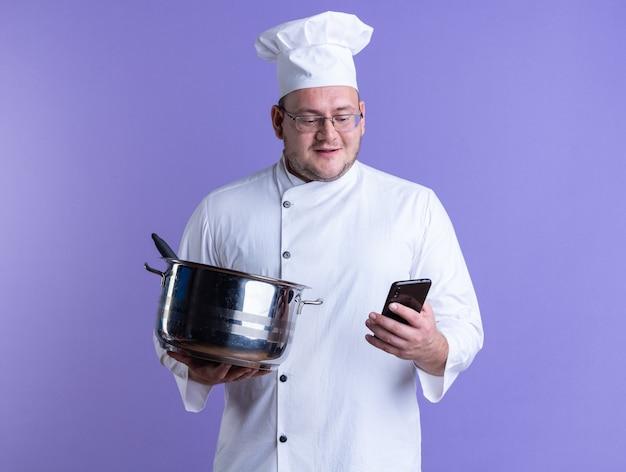 Blij volwassen mannelijke kok met chef-kok uniform en bril met pot en mobiele telefoon kijken naar mobiele telefoon geïsoleerd op paarse muur