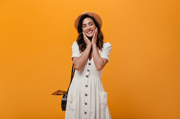 Blij volwassen meisje in witte kledings leuke glimlach op oranje achtergrond. nadenkend vrouw in kleine strooien hoed met zwarte tas poseren.