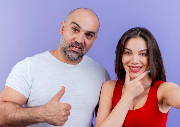 Blij volwassen paar uitziende man duim opdagen en vrouw kin aan te raken