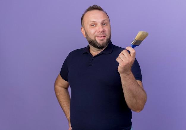 Blij volwassen slavische man hand op taille te zetten en verfborstel geïsoleerd te houden