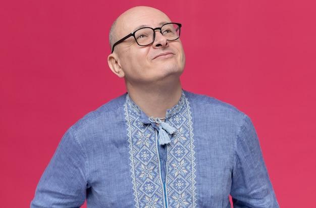Blij volwassen slavische man in blauw shirt met optische bril opzoeken